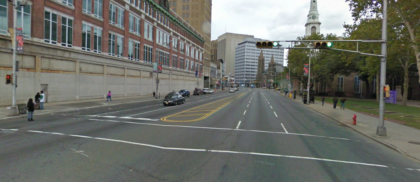 This crosswalk, which leads to Military Park (right) crosses seven lanes of traffic. A crossing island in the center lane would improve safety here. | Photo: Google Maps